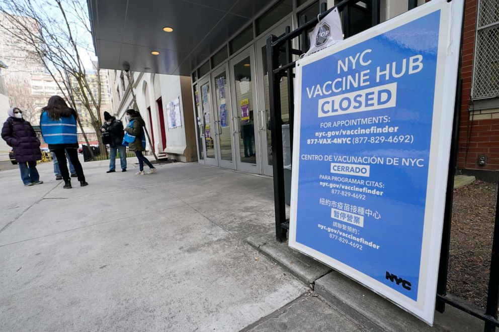 People who had appointments to get COVID-19 vaccinations talk to New York City health care workers, Thursday, Jan. 21, 2021, outside a closed vaccine hub after they were told to come back in a week due to a shortage of vaccines.