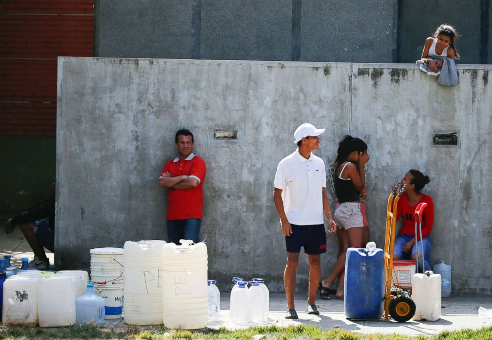 PHOTO: People wait in line to fill up containers with water from a public fountain in Caracas, Venezuela, March 12, 2019.