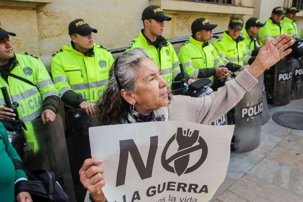 """Police forces stand behind an activist holding a sign that reads """"No to the war in Venezuela, Let's defend life,"""" during a demonstration outside Colombia's Foreign Ministry in Bogota, Feb. 25, 2019."""