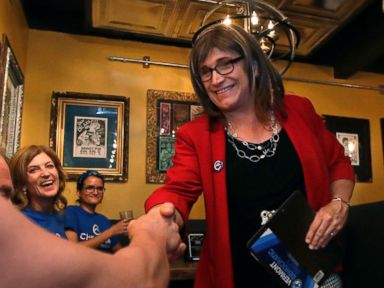 PHOTO: Vermont Democratic gubernatorial candidate Christine Hallquist, holding clipboard, a transgender woman and former electric company executive, shakes hands with her supporters during her election night party in Burlington, Vt., on Aug. 14, 2018.