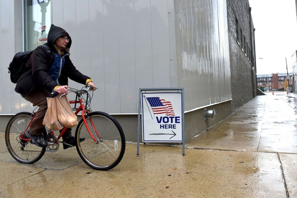 PHOTO: A cyclist passes by a sign directing voters to a polling station in Milwaukee, Nov. 4, 2018.