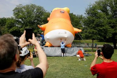 PHOTO: People photograph a Baby Trump balloon as it is moved into position before Independence Day celebrations, July 4, 2019, on the National Mall in Washington.