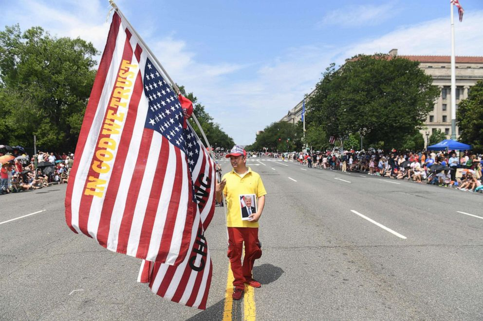 PHOTO: A man holding flags and a photograph of President Donald Trump marches in the Independence Day parade in Washington, D.C., July 4, 2019.