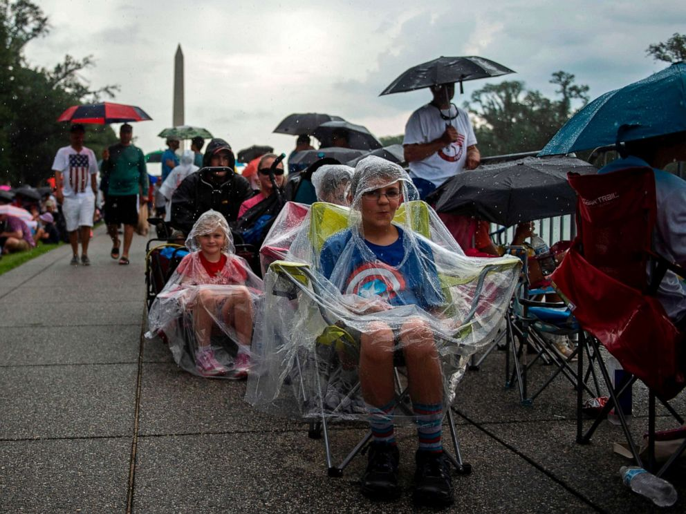 PHOTO: People cover from the rain as they gather on the National Mall ahead of the Salute to America Fourth of July event with President Donald Trump at the Lincoln Memorial in Washington, July 4, 2019.