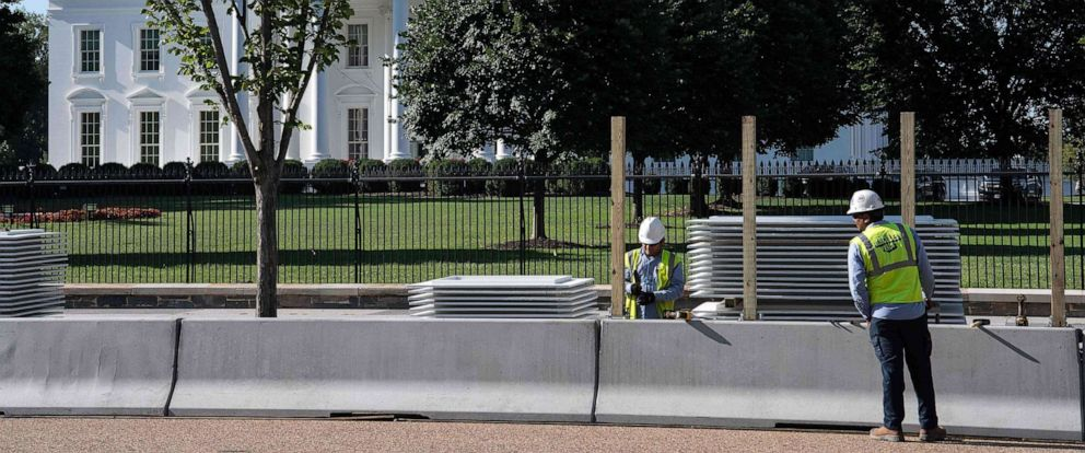 PHOTO: Workers construct a protective barrier ahead of a higher fence being erected in front of the White House in Washington, D.C., July 15, 2019.