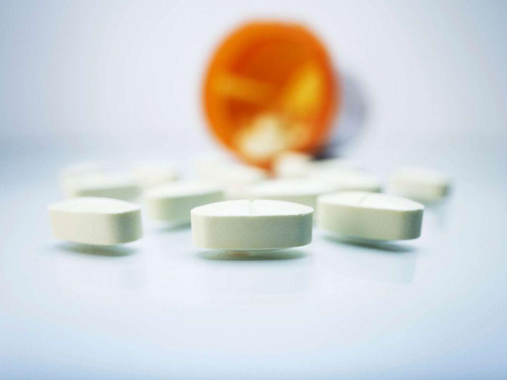 PHOTO: White pills and a plastic prescription pill container.