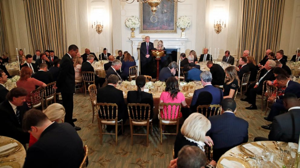 President Donald Trump bows his head in prayer as pastor Paula White leads the room in prayer during a dinner for evangelical leaders in the State Dining Room of the White House, Monday, Aug. 27, 2018, in Washington.