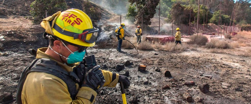 PHOTO: A firefighter from Santa Fe Springs talks on the radio while he battles to control hotspots of the Maria Fire, in Santa Paula, Calif., Nov. 2, 2019.
