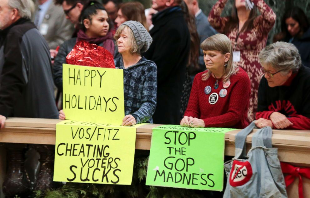 PHOTO: Protesters Peppi Elder, left, and Christine Taylor holds up signs during the state Christmas Tree lighting ceremony in state Capitol Rotunda, Dec. 4, 2018, in Madison, Wis.