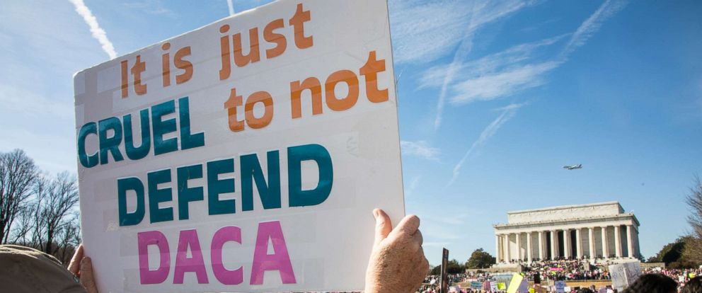 "PHOTO: A demonstrator holds a sign saying ""It is just cruel to not defend DACA"" as thousands of activists gathered on the National Mall and marched to the White House for the 2018 Womens March on Washington D.C., Jan. 20, 2018."