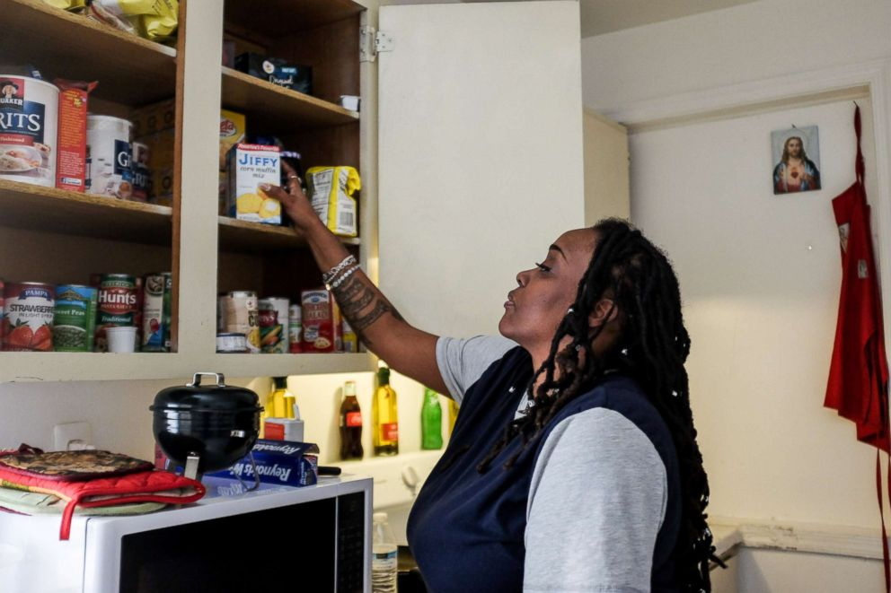 PHOTO: Yvette Hicks looks at free food that she has received from local food banks to feed her children during the shutdown at her apartment in Washington, Jan. 25, 2019.