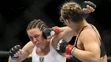 PHOTO: Ronda Rousey hits Alexis Davis during their womens mixed martial arts bantamweight title bout at UFC 175, July 5, 2014, in Las Vegas.