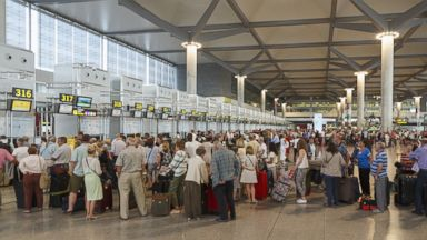 PHOTO: People wait at the airport check-in queues in Malaga, Spain.