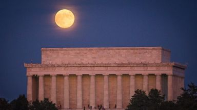 PHOTO: People watch the sunset from the Lincoln Memorial in Washington as a full moon raises in the background on Oct. 18, 2013.