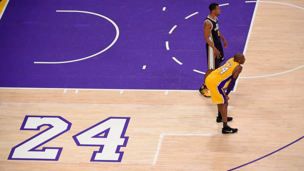 Los Angeles Lakers forward Kobe Bryant, foreground, and Utah Jazz guard Rodney Hood pause during the first half of Bryant's last NBA basketball game, April 13, 2016, in Los Angeles.