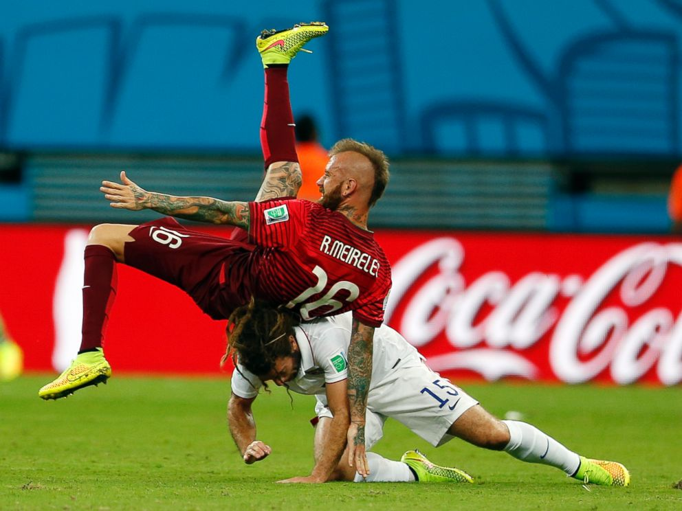 PHOTO: Portugals Raul Meireles falls on top of United States Kyle Beckerman during the group G World Cup soccer match between the United States and Portugal at the Arena da Amazonia in Manaus, Brazil, Sunday, June 22, 2014.