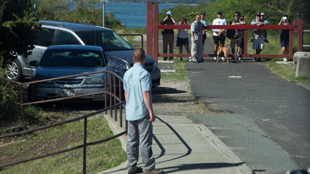 People vie to see past a secret service agent for a glimpse of the motorcade taking President Barack Obama and the first family to Hanauma Bay Nature Preserve where they will go snorkeling, according to the White House, Jan. 1, 2015, on the island of Oahu in Hawaii during the Obama family vacation.