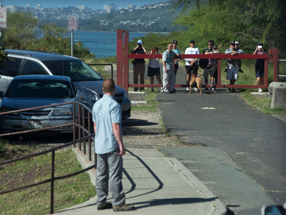 PHOTO: People vie to see past a secret service agent for a glimpse of the motorcade taking President Barack Obama and the first family to Hanauma Bay Nature Preserve, Jan. 1, 2015, on the island of Oahu in Hawaii.