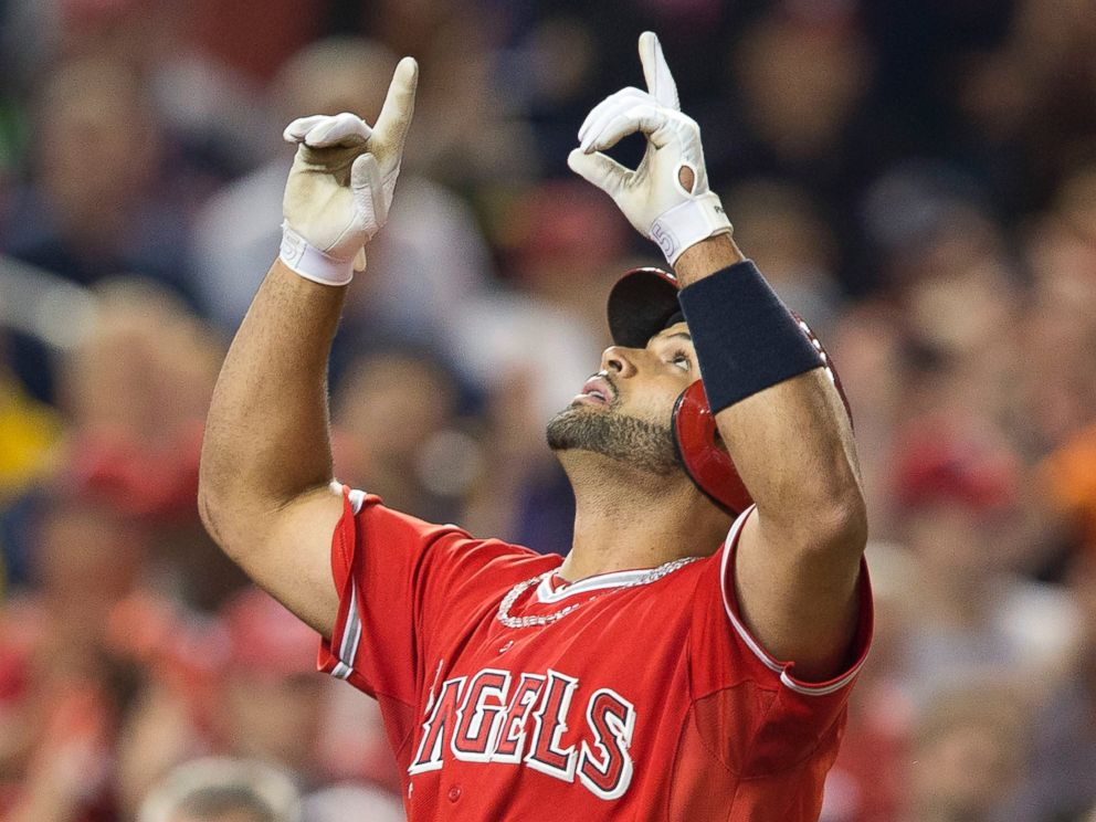 PHOTO: Albert Pujols points upward as he crosses home plate after hitting his 500th career home run, April 22, 2014.