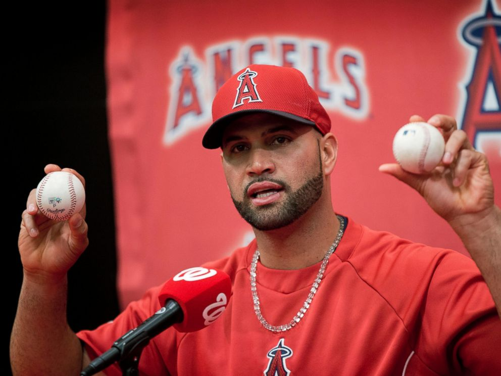 PHOTO: Los Angeles Angels Albert Pujols holds up the balls that he hit for his 499th, right, and 500th, left, career homers, April 22, 2014.