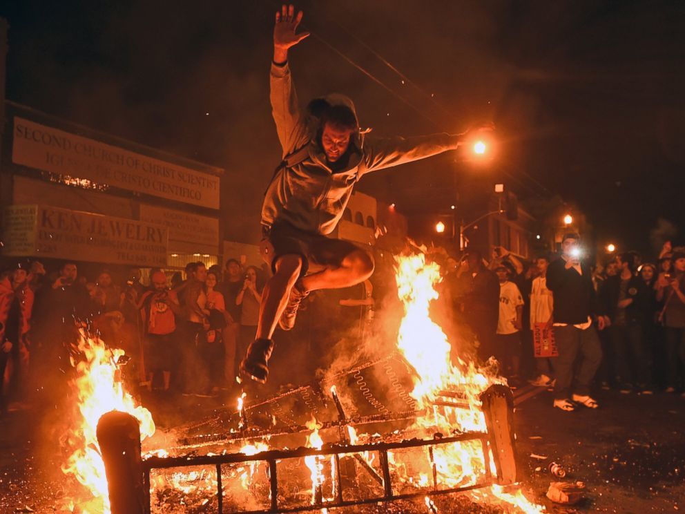 A man jumps over some debris that has been set on fire in the Mission district after the San Francisco Giants beat the Kansas City Royals to win the World Series on Wednesday, Oct. 29, 2014, in San Francisco.