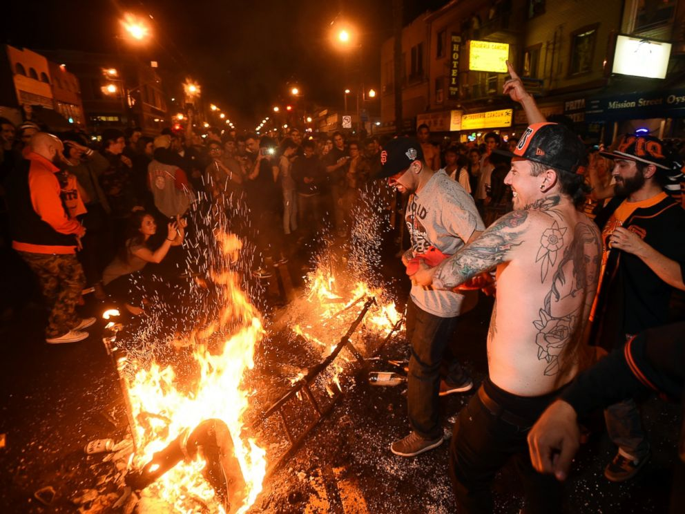 San Francisco Giants fans celebrate next to debris that has been set on fire in the Mission district after the San Francisco Giants beat the Kansas City Royals to win the World Series on Wednesday, Oct. 29, 2014, in San Francisco.