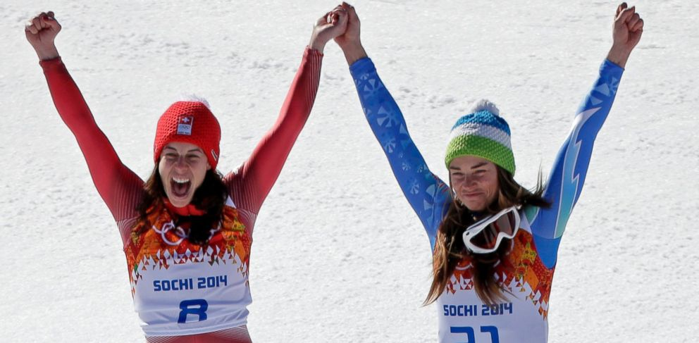 PHOTO: Womens downhill gold medal winners Switzerlands Dominique Gisin, left, and Slovenias Tina Maze stand together on the podium during a flower ceremony at the Sochi 2014 Winter Olympics, Wednesday, Feb. 12, 2014, in Krasnaya Polyana, Russia.