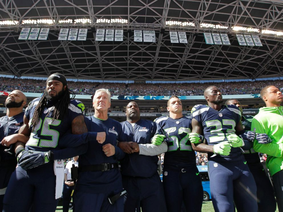 PHOTO: Seattle Seahawks players and coaches stand and link arms during the singing of the national anthem before an NFL football game against the Miami Dolphins, Sept. 11, 2016, in Seattle.