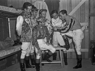 PHOTO: Jockey Eddie Arcaro tells his fellow horse pilots, from left, Buddy Haas, Porter Roberts, Jimmy Stout, Don Meade and Johnny Gilbert, how he guided Warren Wrights Whirlaway to victory in both the Kentucky Derby and The Preakness Stakes.
