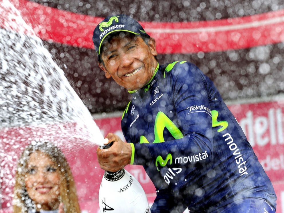 PHOTO: Colombias Nairo Quintana sprays champagne on the podium as he celebrates winning the 16th stage of the 97th Giro dItalia (Tour of Italy) cycling race, 139 km from Ponte di Legno to Val Martello, on May 27, 2014 in Val Martello.