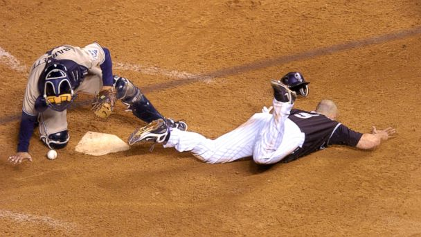 PHOTO: Matt Holiday slides past the plate to score the winning run as Padres catcher Michael Barrett drops the ball in the Rockies 13th inning victory at Coors Field in Denver, Oct. 1, 2007.