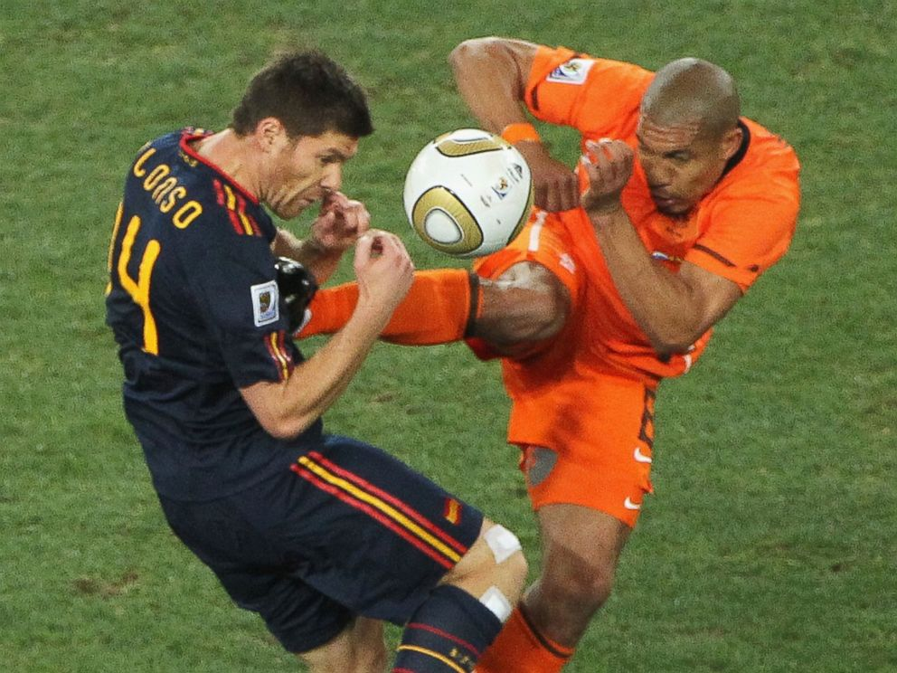 PHOTO: Nigel de Jong, right, of the Netherlands tackles Xabi Alonso, center, of Spain with a kick in the chest during the 2010 World Cup on July 11, 2010 in Johannesburg, South Africa.