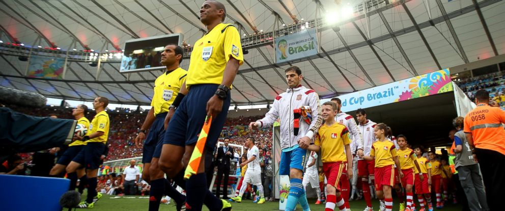 PHOTO: Iker Casillas of Spain leads his team to the field with their player escorts during the 2014 FIFA World Cup Brazil Group B match between Spain and Chile at Maracana on June 18, 2014 in Rio de Janeiro, Brazil.