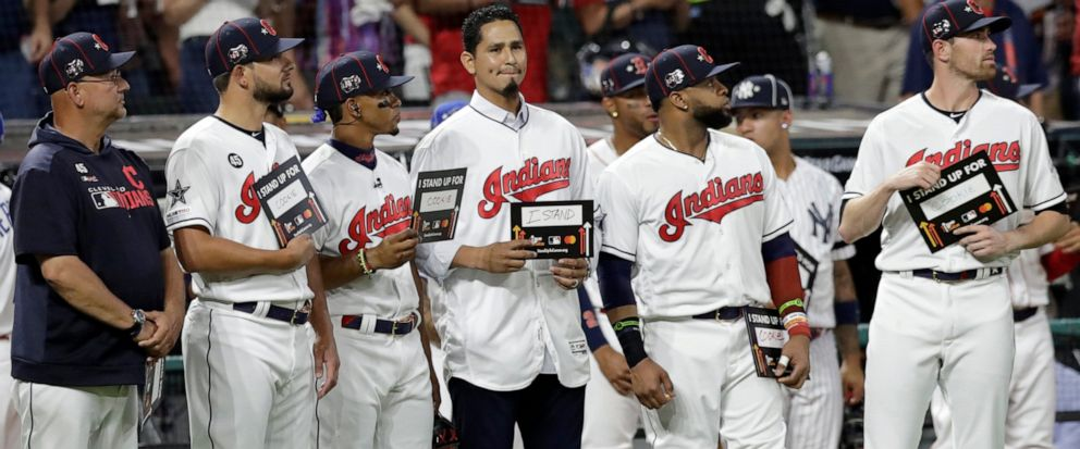 """FILE - In this July 9, 2019, file photo, Cleveland Indians pitcher Carlos Carrasco, center without a hat, stands with Indians teammates during the fifth inning of the baseball All-Star Game in Cleveland, as part of Major League Baseballs """"Stand Up t"""