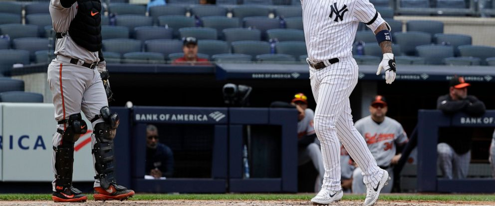New York Yankees Gleyber Torres, right, gestures as he runs past Baltimore Orioles catcher Austin Wynns, left, after hitting a home run during the fourth inning of a baseball game Wednesday, May 15, 2019, in New York. (AP Photo/Frank Franklin II)