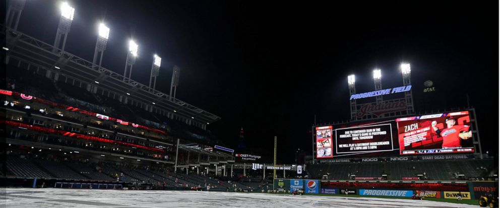 The tarp rests on the field after a baseball game between the Minnesota Twins and the Cleveland Indians is postponed due to the weather, Friday, Sept. 13, 2019, in Cleveland. The Indians and Twins will play a doubleheader on Saturday. (AP Photo/Tony