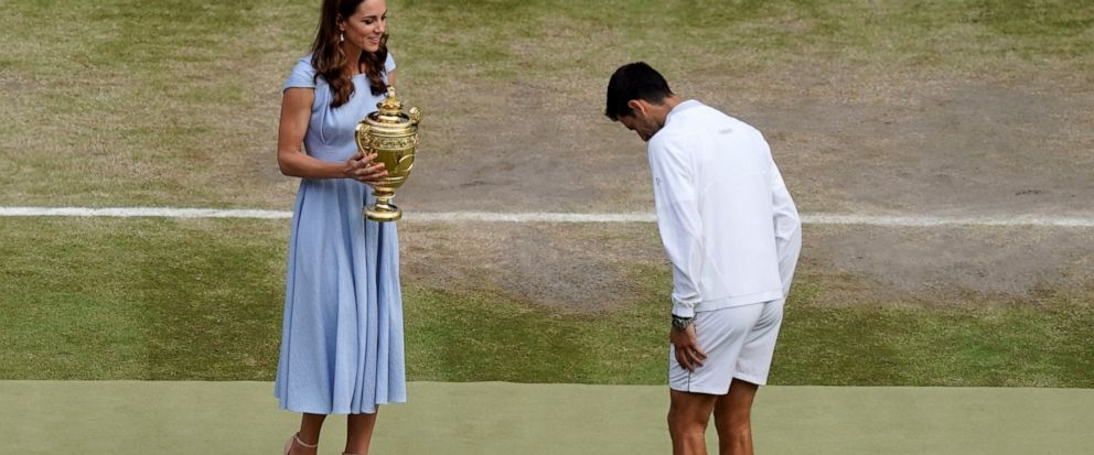 Serbias Novak Djokovic bows to Britains Kate, Duchess of Cambridge before being presented with the winners trophy after defeating Switzerlands Roger Federer during the mens singles final match of the Wimbledon Tennis Championships in London, Sund