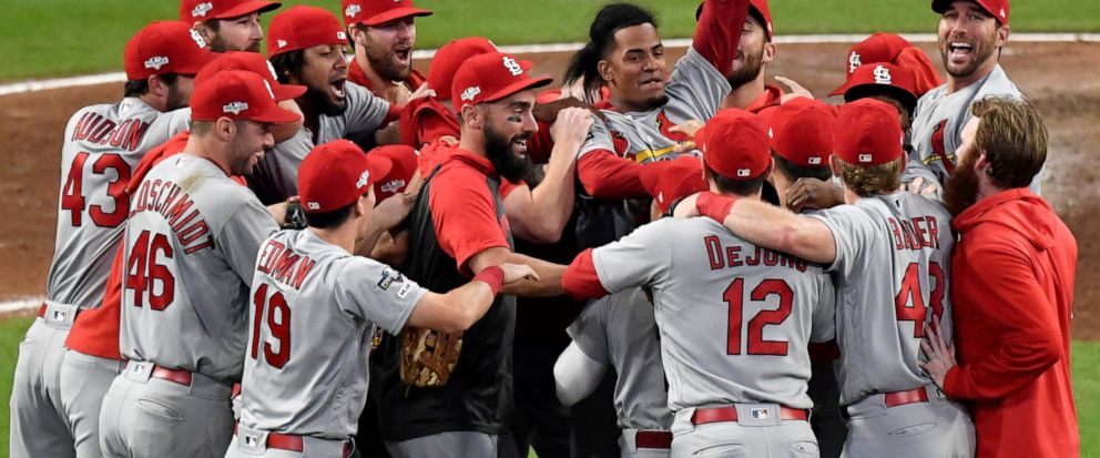 St. Louis Cardinals relief pitcher Genesis Cabrera waves his hat in the air as he celebrates with teammates after the Cardinals beat the Atlanta Braves 13-1 in Game 5 of their National League Division Series baseball game Wednesday, Oct. 9, 2019, in