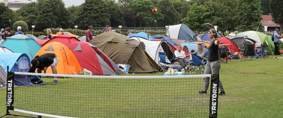 In this Tuesday, July 9, 2019, some tennis fans play a game as they wait in line for tickets to enter the Wimbledon Tennis Championships in London. For many the Wimbledon experience starts in a tent as they gather in a small park across from the tour