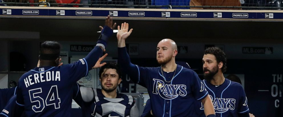 Tampa Bay Rays Guillermo Heredia (54) is greeted by teammates after scoring off a fly ball by Jesus Aguilar during the seventh inning of a baseball game against the San Diego Padres Monday, Aug. 12, 2019, in San Diego. (AP Photo/Gregory Bull)