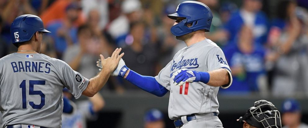 Los Angeles Dodgers A.J. Pollock celebrates his two-run with Austin Barnes (15) during the sixth inning of a baseball game as Baltimore Orioles catcher Pedro Severino kneels at right, Wednesday, Sept. 11, 2019, in Baltimore. (AP Photo/Nick Wass)