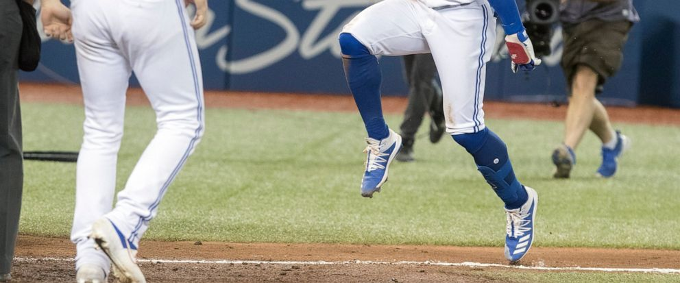 Toronto Blue Jays designated hitter Bo Bichette, front right, rounds the bases after hitting a walkoff home run to defeat the New York Yankees in the 12th inning of a baseball game in Toronto, Friday, Sept. 13, 2019. (Fred Thornhill/The Canadian Pres