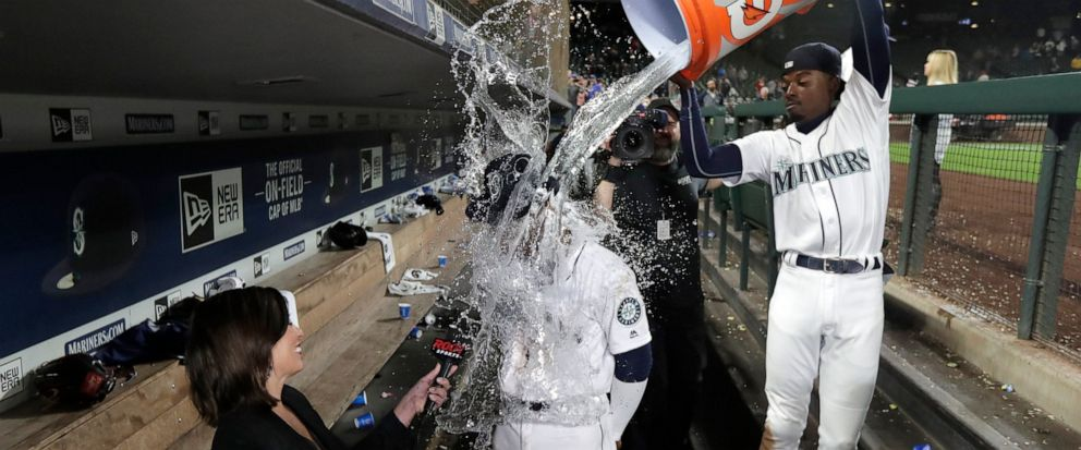 Seattle Mariners right fielder Kyle Lewis, center, is doused with water by Dee Gordon, right, as Lewis takes part in an interview following the teams baseball game against the Cincinnati Reds, Tuesday, Sept. 10, 2019, in Seattle. Lewis hit a solo ho