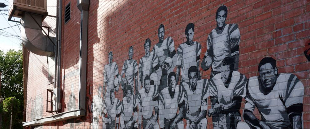 In this Wednesday, Sept. 11, 2019 photo shows part of an alleyway mural in downtown Laramie, Wyo., that honors the Black 14. The Black 14 were black athletes dismissed from the University of Wyoming football team in 1969 for seeking to protest racism