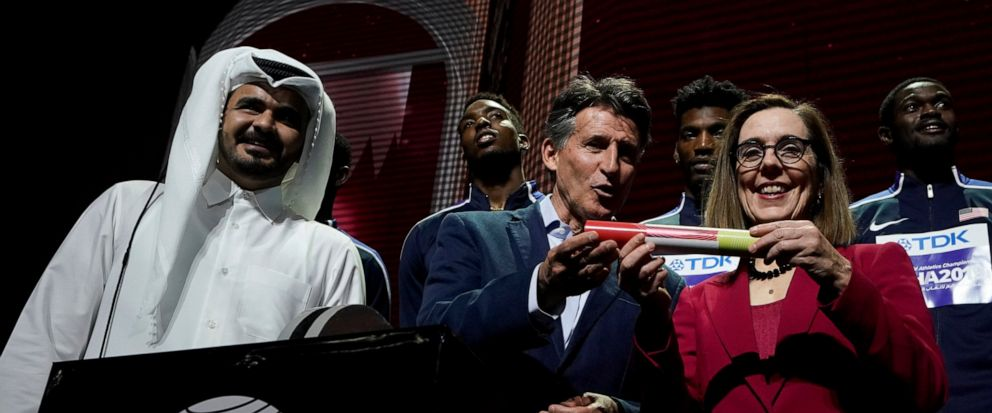 Sheikh Joaan bin Hamad bin Khalifa Al Thani, IAAF President Sebastian Coe hands over a ceremonial baton to Oregon Governor Kate Brown pose at the closing ceremony for the World Athletics Championships in Doha, Qatar, Sunday, Oct. 6, 2019. (AP Photo/M