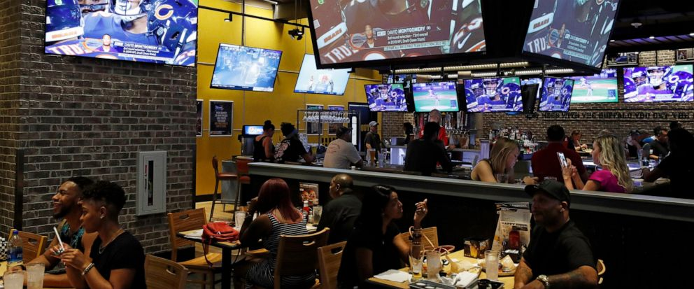 People eat and watch football at a Buffalo Wild Wings, Thursday, Sept. 5, 2019, in Las Vegas. MGM Resorts International and Buffalo Wild Wings are launching a mobile football game app for customers to pick favorite NFL teams, choose weekly fantasy pe