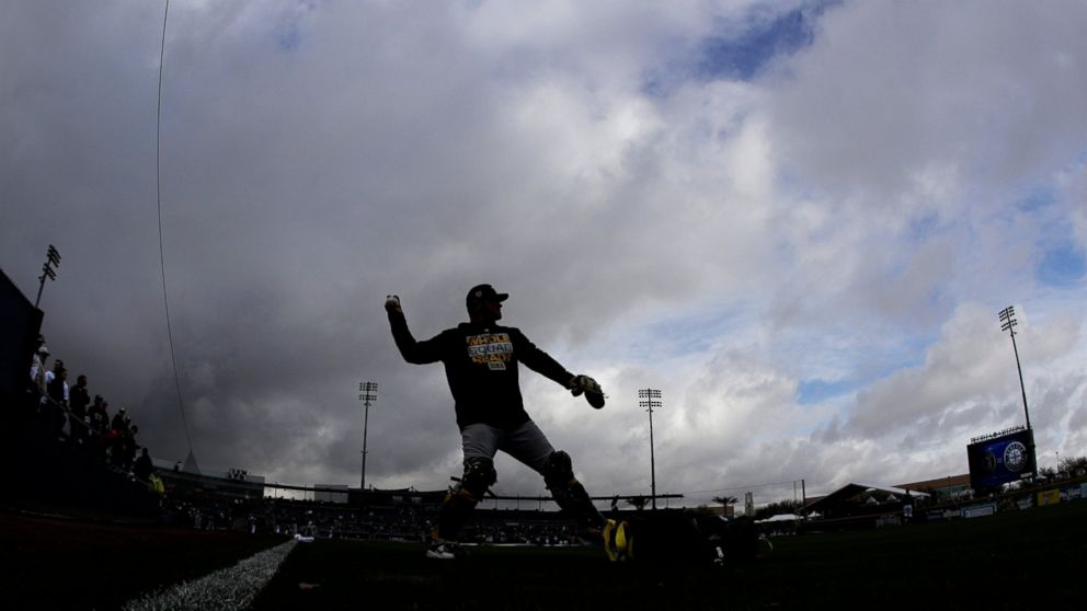 Oakland Athletics catcher Chris Herrmann is silhouetted against storm clouds as he warms up before a spring training baseball game against the Seattle Mariners, Friday, Feb. 22, 2019, in Peoria, Ariz. (AP Photo/Charlie Riedel)
