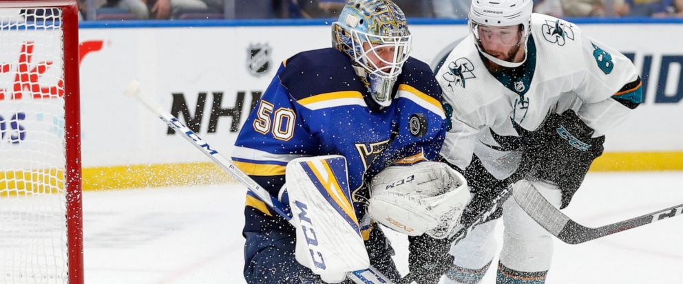 St. Louis Blues goaltender Jordan Binnington (50) protects the puck as San Jose Sharks center Melker Karlsson (68), of Sweden, closes in during the second period in Game 4 of the NHL hockey Stanley Cup Western Conference final series Friday, May 17,