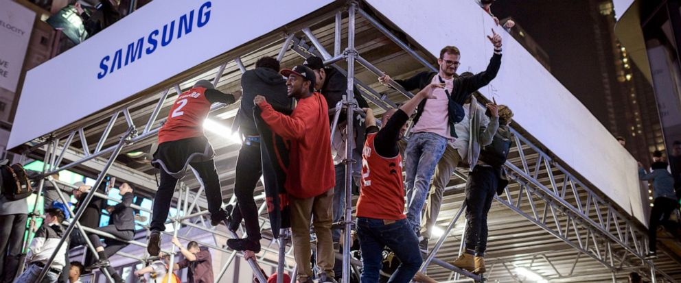 Toronto Raptors supporters climb a scaffold as fans celebrate in the streets after the Raptors defeated the Golden State Warriors during Game 6 NBA Finals to win the NBA Championship, in Toronto on Thursday, June 13, 2019. (Christopher Katsarov/The C