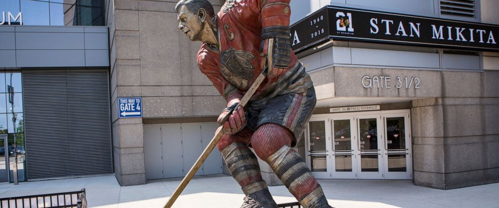 FILE - In this Aug. 12, 2018, file photo, flowers are left to honor former Chicago Blackhawk Stan Mikita on his statue outside United Center in Chicago. A posthumous study of Mikitas brain shows the hockey Hall of Famer suffered from chronic traumat